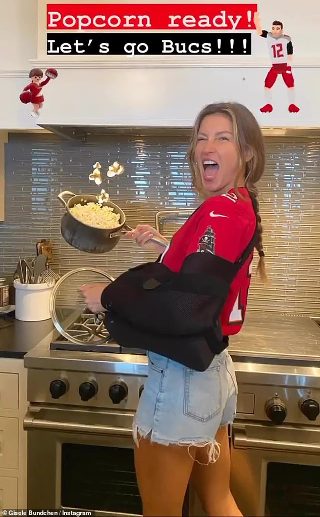 Team player: Gisele Bündchen, 40, sported a new black arm sling as she made some popcorn and cheered on her husband Tom Brady ahead of his game