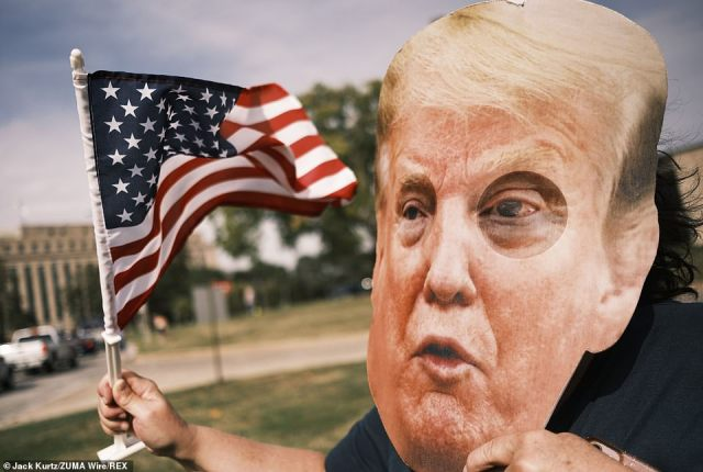 A person wearing a large President Donald Trump mask wave to people in a motorcade supporting the president's reelection