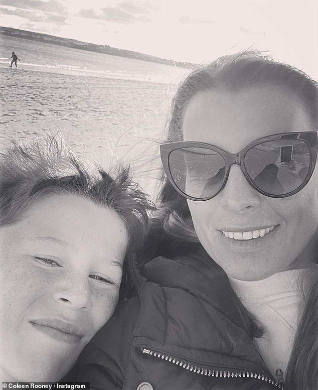 Like mother like son: Coleen Rooney beamed as she posed on the picturesque shorefront with her 10-year old son Kai on Sunday