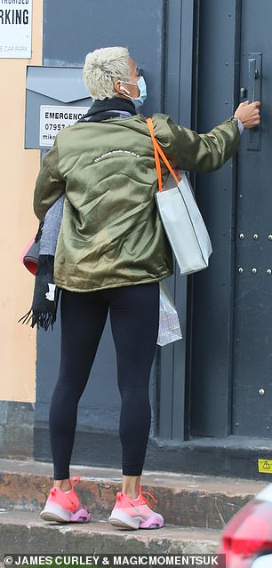 Style:She added a simple pair of black leggings and bright pink trainers to her look, while she covered her face with a disposable mask