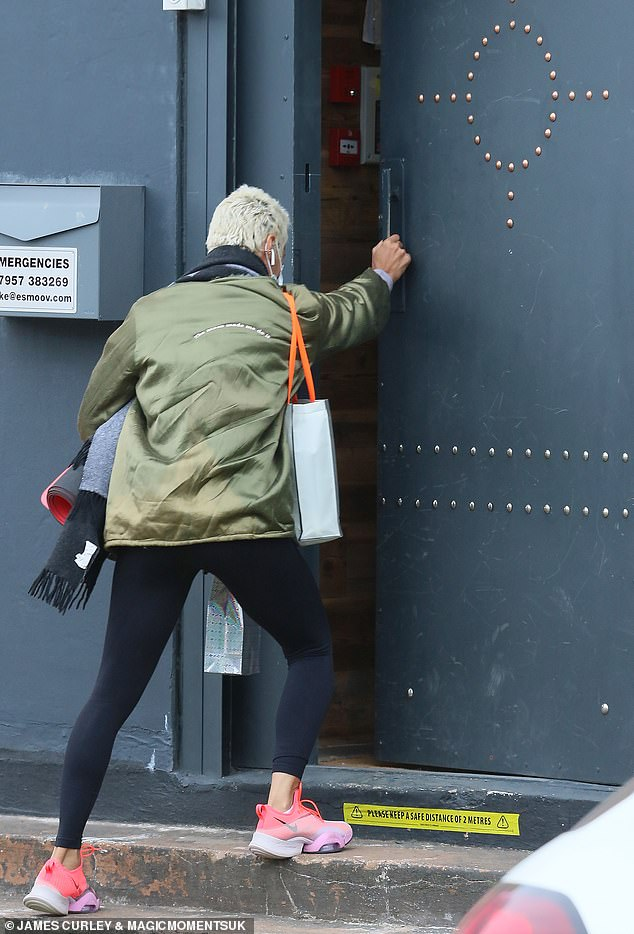 Easy does it: The platinum-haired star at first appeared to struggle with the door before being helped inside