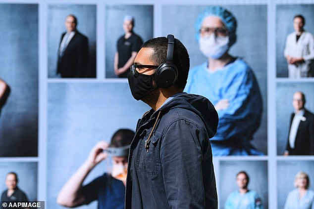 A man walks past an outdoor photography exhibition of healthcare workers in Melbourne last Tuesday. Face masks are now mandatory in Victoria - a plastic face shield is not enough