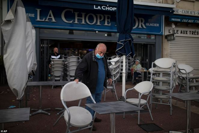 The strict measures have continued across France including in Marseille where bars and restaurants have been ordered to close for a week. Pictured: Restaurant owner packs away chairs in Marseille
