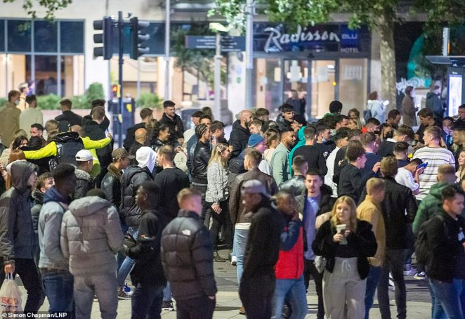 The new measures have striking resemblance to those introduced across the UK by Boris Johnson. Pictured: Crowd of people spill out into the street in Bristol after the 10pm curfew early closing of pubs and bars