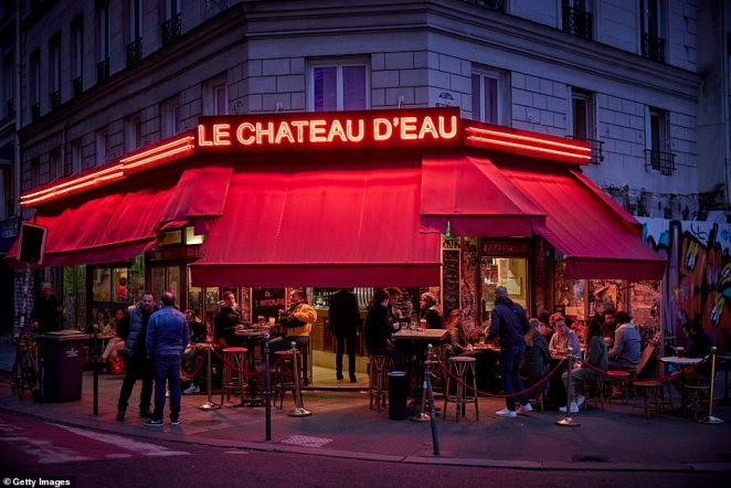 Paris is set to enter a strict second lockdown in attempt to slow the spike in coronavirus cases. Pictured: Parisians drinking outside at a bar last night before the restrictions bare introduced
