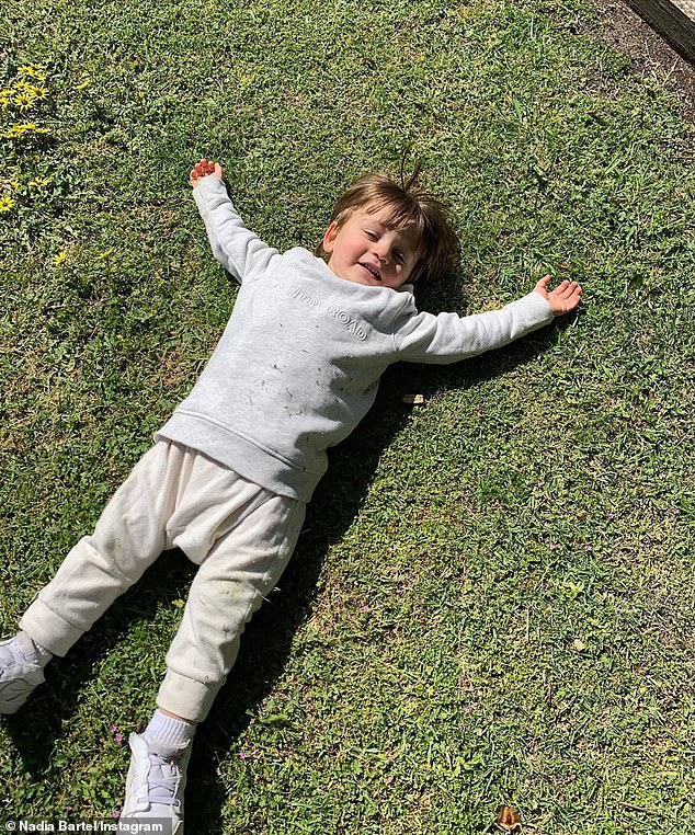 Child's play: Nadia's son Henley looked to be having fun in the sun while at the park