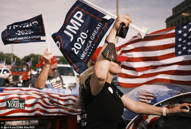 People supporting the reelection of Trump are seen in the parking lot in the Iowa State Capitol