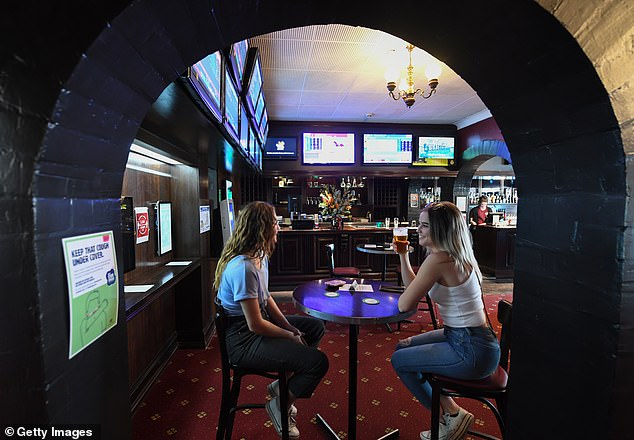 Clubs and pubs are hoping to double the amount of patrons allowed inside after NSW went two days without any new coronavirus cases (pictured two women enjoy at drink at the Royal Hotel in Sydney)