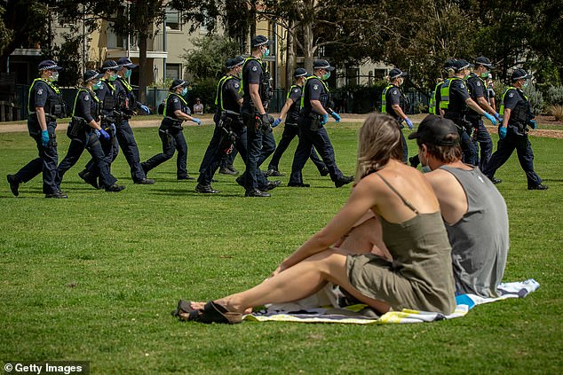 Two Melburnians sit in Elsternwick Park while police walk by. Gatherings of up to 10 people in public and up to five people at home are permitted in Melbourne, with fines of up to $4,957 for those who break the rules