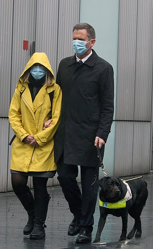 Lord Christopher Holmes with his guide dog and a woman believed to be his wife outside Southwark Crown Court