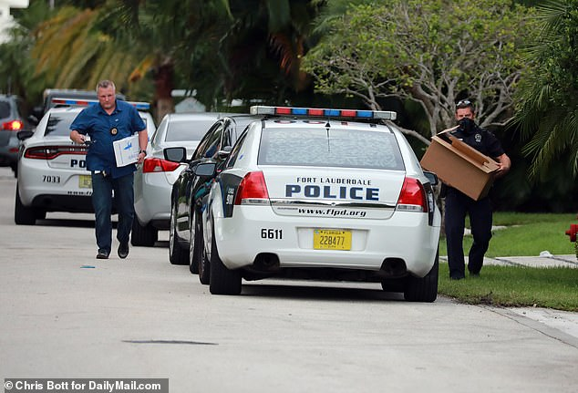 As many as 20 police cars and boats swarmed the waterfront property after the distraught wife told cops she heard a revolver being cocked and a 'loud boom' after Parscale began 'ranting and raving'. Pictured: Police remove evidence and what looks like a rifle and possibly other guns from Parscale's home