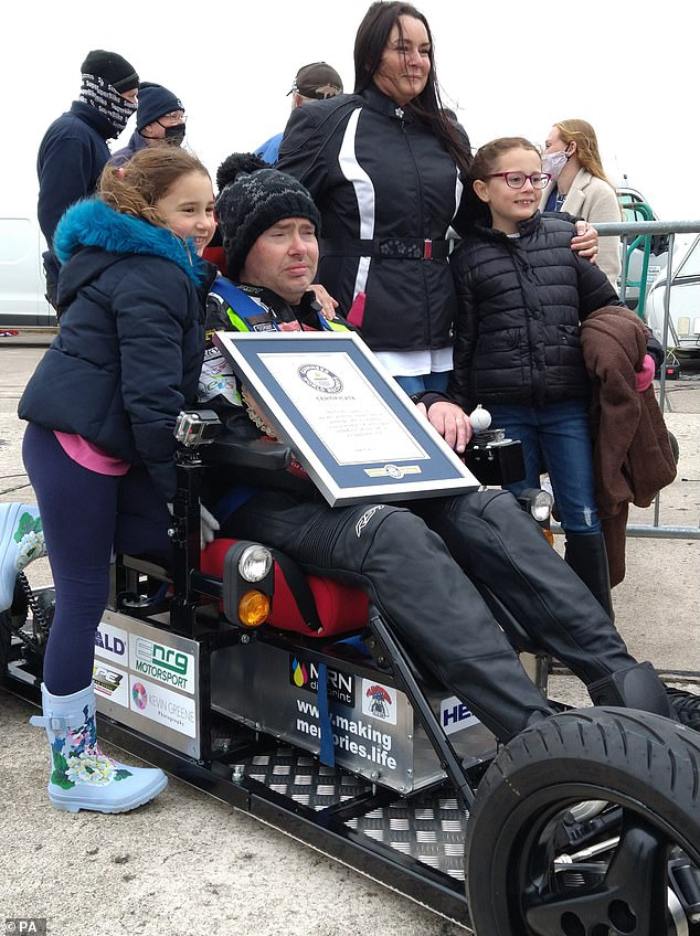 Proud: Jason Liversidge with his family after exceeding the previous record of 62mph and reaching 66.826mph in his wheelchair