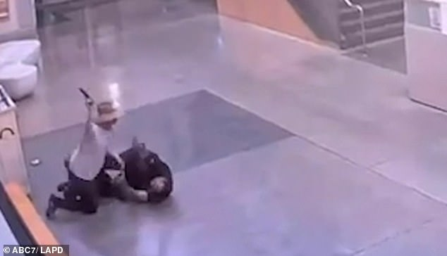 The assailant is seen above pistol-whipping the desk officer as he lay on the ground in the police station