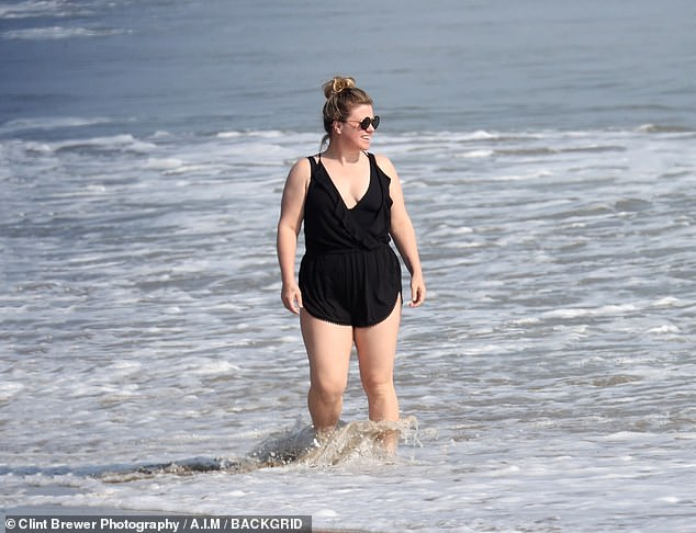 Hot mama: Over the weekend the Grammy-winner seemed carefree as she hung out with friends and took a dip in the Pacific wearing a classic black one-piece swimsuit underneath a trendy black cotton romper