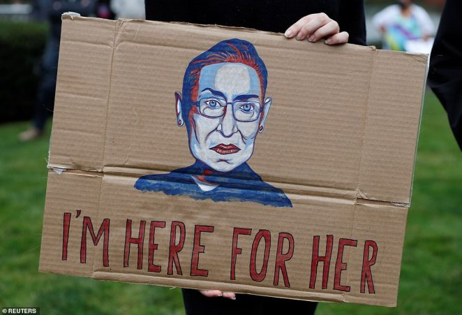 A protester holds up a sign in honor of the late Supreme Court Justice Ruth Bader Ginsburg