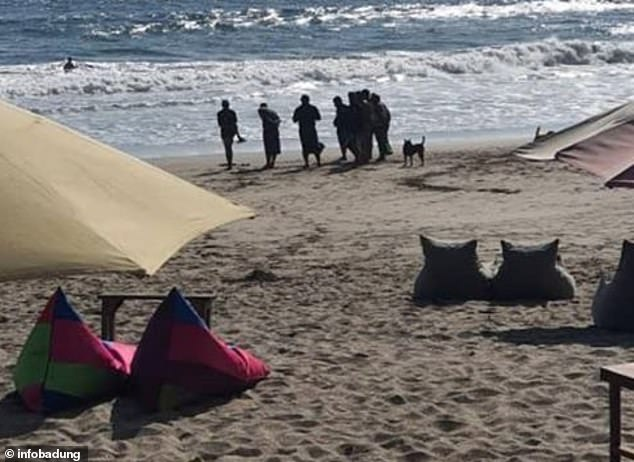 The foot was found by a foreigner and locals (pictured) who were enjoying the afternoon sun on the popular Bali beach, police have urged anyone with information to come forward