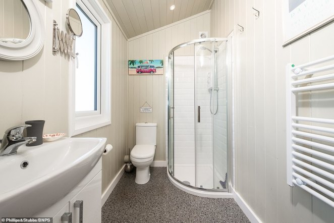 The shower room has matchboard panelled walls and a white suite with corner shower enclosure, wash basin with vanity unit and a close coupled WC