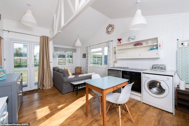 The kitchen area has been re-modelled in a 'retro 1960's style' with Daintymaid wall and base cabinets, granite-effect working surfaces, single bowl, double drainer stainless steel sink, inset electric hob and built-in oven, washing machine and fridge