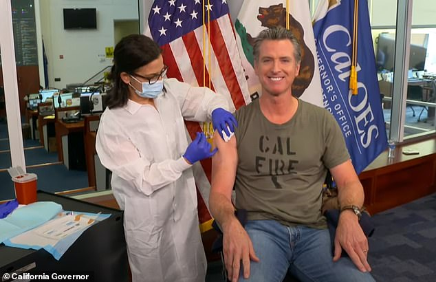 California's Democratic governor Gavin Newsom broke off from a live press conference to have a flu jab (pictured) as he warned of a possible 'twindemic' of influenza and Covid-19