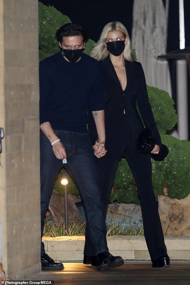 Chic: Nicola, 25, wore a plunging black pantsuit and heels, with the couple both sporting black masks