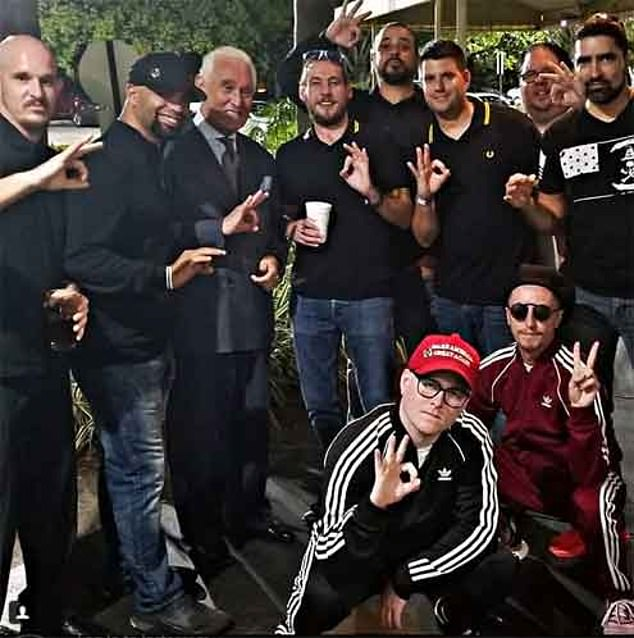 Roger Stone is picture with a group of the Proud Boys as they hold up the 'white power' symbol with their hands.The unofficial uniform of the Proud Boys is a black and yellow Fred Perry polo shirt – which is, bizarrely, a clothing choice they share with many in the gay BDSM community