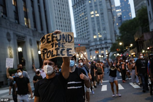 A protester holds a sign saying 'defund the police' at a protest backing Black Lives Matter in New York. Meghan said she thought peaceful protests were 'beautiful' but said she accepted some people found them 'inflammatory'