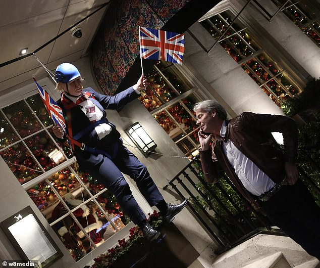 Richard Caring positioned two figures of Boris Johnson waving Unions Jacks outside his Mayfair restaurant as it reopened today, recreating the PM's infamous zip wire stunt