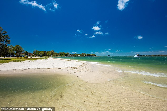 A man wanted for shooting a woman in the back on an idyllic island (pictured) was dramatically arrested after a teenage girl found him hiding in her holiday home