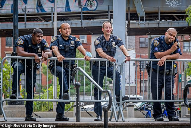 The mayor on Thursday admitted he did not know how many cops have been penalized so NYPD officers have been spotted out and about without a face covering in recent months. Pictured: Cops at a Brooklyn protest on September 13