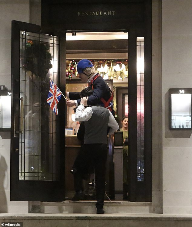 Workers move the Boris Johnson figures at Richard Caring's Mayfair restaurant on Thursday evening