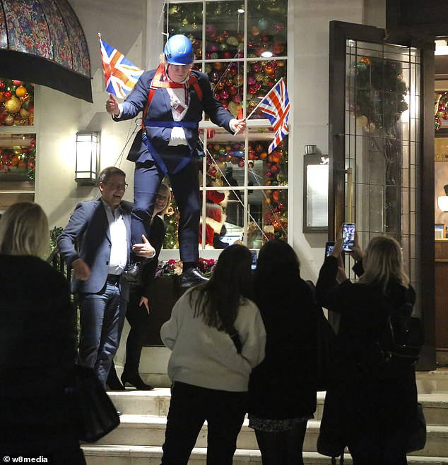 Diners and passers-by take photos of a Boris Johnson mannequin at Richard Caring's Mayfair restaurant