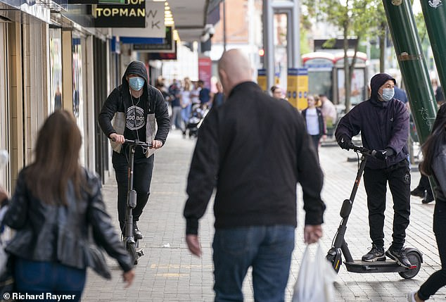 Two riders of rented e-scooters wearing covid masks as a disguise drive through the pedestrianised town centre of Middlesbrough