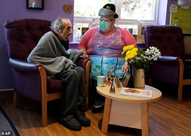 Amnesty International's report will show that Ministers 'knew from the outset' that Covid-19 posed an exceptional danger to the 400,000 residents of UK care homes, many of whom are frail and live with multiple health conditions(pictured, a nurse sitting beside a resident of Wren Hall care home in Selston)