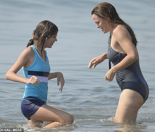 The blues: Violet stayed close to her mother in the water, while sporting a neon blue tank top with navy blue and white stripes, teamed with matching navy shorts