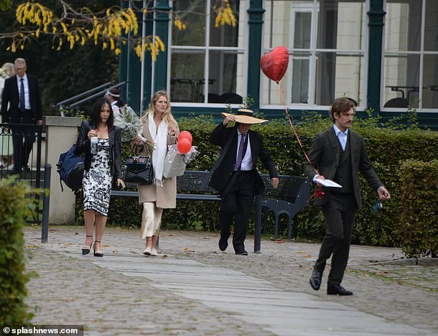 New beginning: Toni added a chic beige coat over her slip dress as she left the venue while Alex carried a love heart balloon