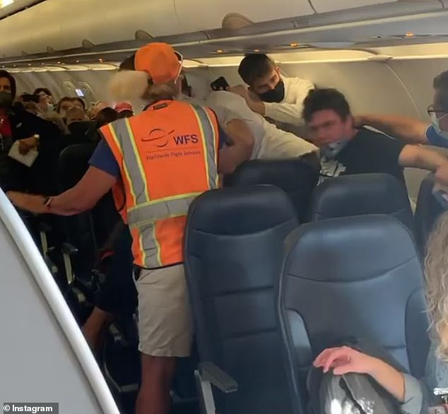 A second passenger (right), got angry with the older man (center) and confronted him before the flight took off from Mesa, Arizona, to Provo, Utah.