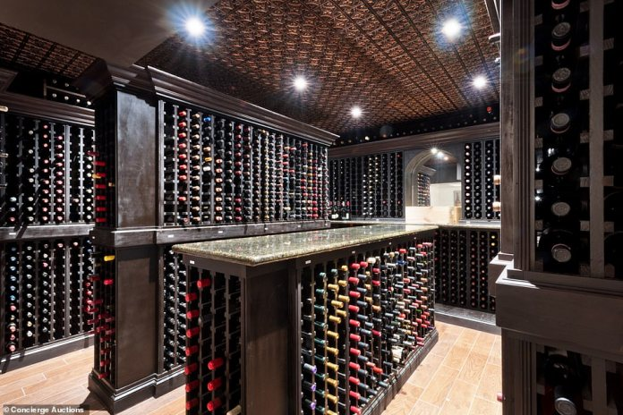 The property has a secluded 5,000-bottle wine cellar with a tasting room, while a secret door from the mahogany office leads to a rooftop deck