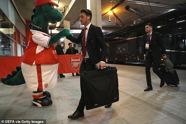 Ozil pictured shaking hands with Gunnersaurus ahead of a match at the Emirates Stadium