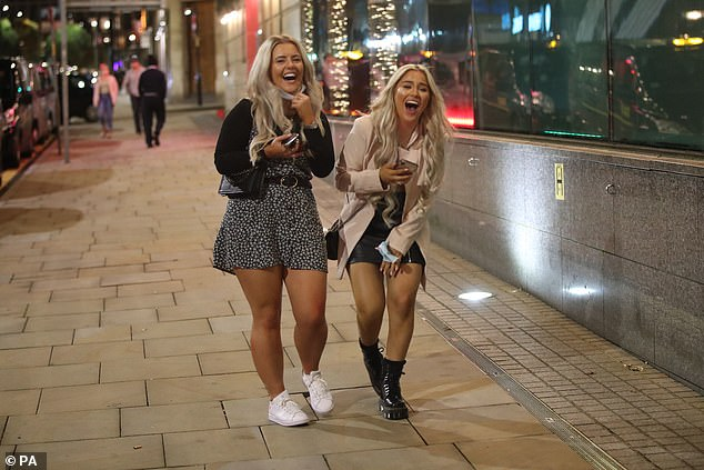Two women were seen laughing as they walked along the pavement in Manchester. Partygoers were enjoying a night out