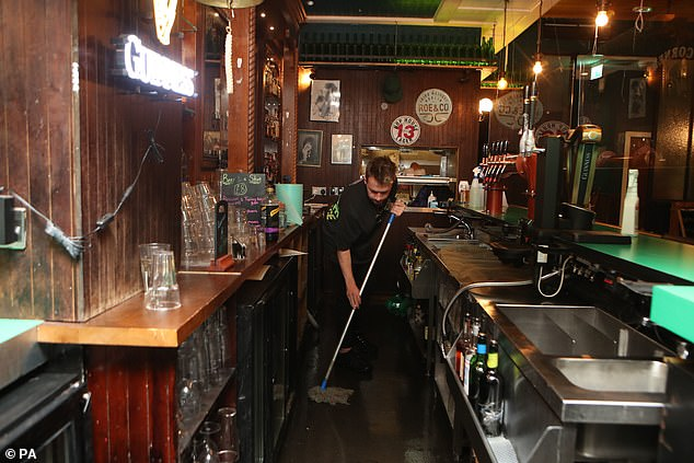 A staff member in The Corner Boy pub mopping the floor as he closes up for the evening