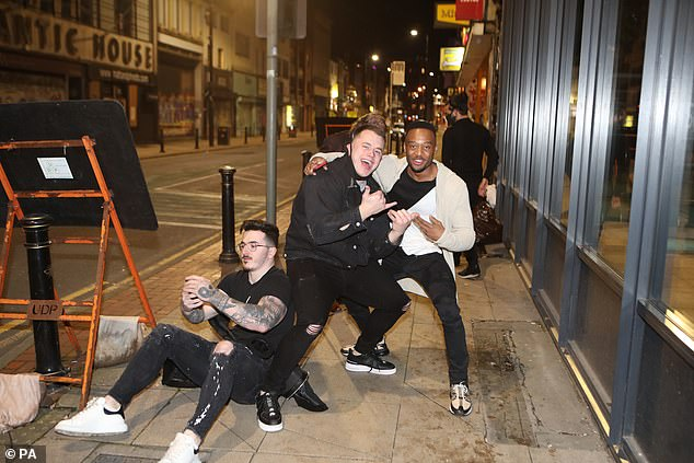 Three partygoers - one seated on the pavement - pose for pictures as they enjoy a night out in Manchester on Sunday