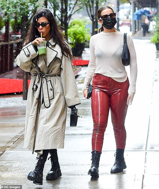 Good times: The 41-year-old reality TV star braved the rain in a sturdy trench coat while Addison, 20, wore red patent leather pants and a sweater