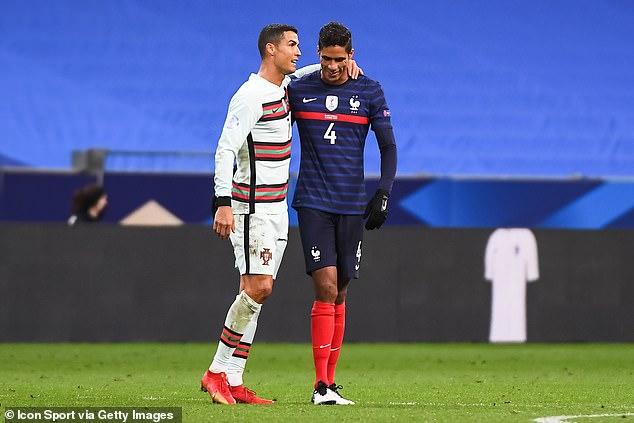 Ronaldo puts an arm around Real Madrid and French defender Raphael Varane on Sunday