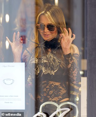 Sensational: She dressed up in a sheer black lace bodysuit as she visited the shop