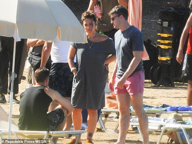 Hunky: Paul, 24, looked typically cool in a grey T-shirt, pink swimming trunks and his signature shades
