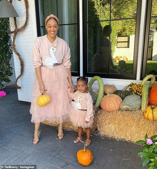 Pumpkin fun: Tia Mowry, 42, smiles with her two-year-old daughter Cairo in matching pink outfits, as they pose in front of the actress's  tasteful pumpkin display at their Los Angeles home for some fall fun