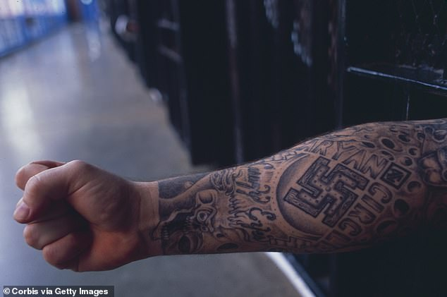 Two dozen people, including 12 alleged members of the Aryan Circle, were indicted in federal courts on Wednesday. Pictured: An Aryan Circle white supremacist gang member showing off his gang tattoo in a Texas prison
