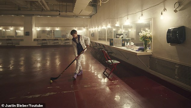 Hockey: The young Bieber then stands up and grabs a hockey stick next to him, stick-handling the tennis ball as he walks before passing it off and setting the stick down