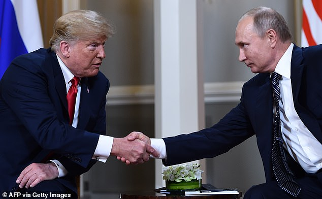 Russian President Vladimir Putin (R) and US President Donald Trump shake hands before a meeting in Helsinki, on July 16, 2018. Sasse said Trump 'kisses dictators' butts'