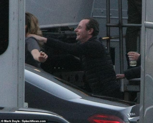 Fun: She danced around with one of the film's crew as they headed onto the set